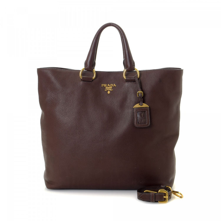 0d9c52f6ecef LXRandCo guarantees this is an authentic vintage Prada Two Way tote.  Crafted in vitello daino leather, this iconic work bag comes in dark brown.