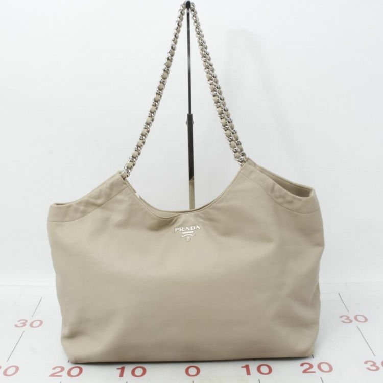 48ec77a195e8 LXRandCo guarantees the authenticity of this vintage Prada Chain tote.  Crafted in nappa leather, this signature bag comes in beige. Good  condition* (AB)
