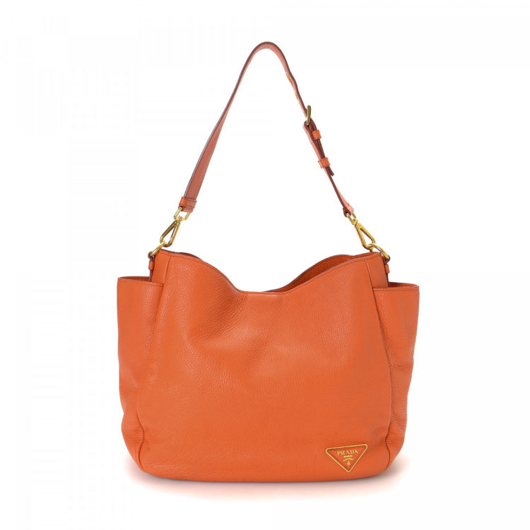 cedee86a5ef3 The authenticity of this vintage Prada shoulder bag is guaranteed by  LXRandCo. This refined shoulder bag in orange is made in vitello daino  leather.