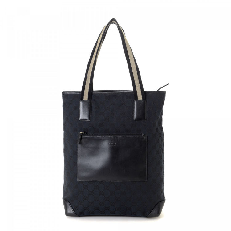 6cd79d97792 LXRandCo guarantees the authenticity of this vintage Gucci tote. This  iconic work bag was crafted in gg canvas in beautiful navy. Due to the  vintage nature ...