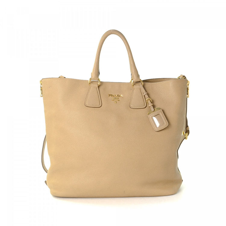 43360c4350ab The authenticity of this vintage Prada Two Way tote is guaranteed by  LXRandCo. This stylish work bag in beige is made in vitello daino leather.