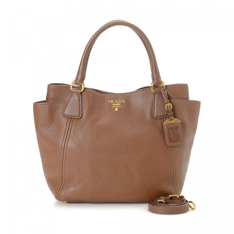 26486edcb3fa The authenticity of this vintage Prada Two Way tote is guaranteed by  LXRandCo. This elegant work bag in beautiful brown is made in vitello daino  leather.
